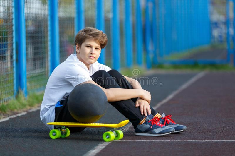 Cute young sport boy with yellow skateboard. He has a good time on his free time on weekend, holidayson sports ground. royalty free stock photography