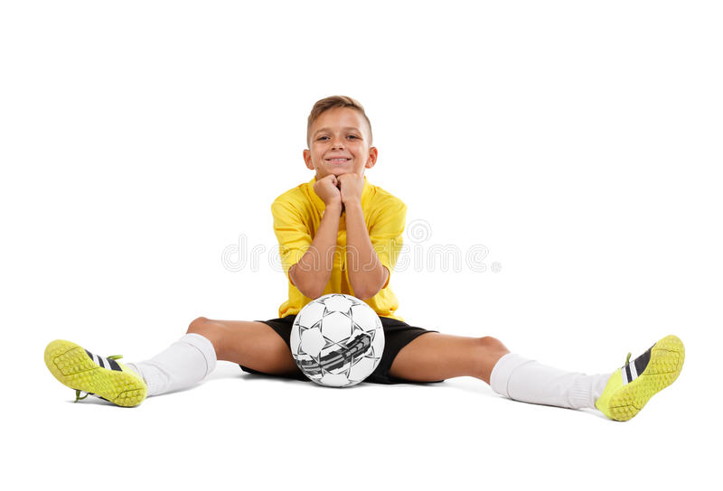 A cute young sportsman in a yellow T-shirt and black shorts sitting on a floor isolated on a white background. stock image