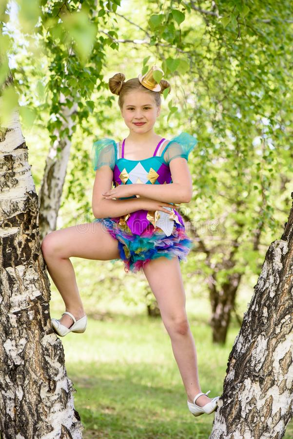 Cute young sporty blond girl standing between two birch trees, wears colorfull sport swimsuit and gold bowler hat royalty free stock photography