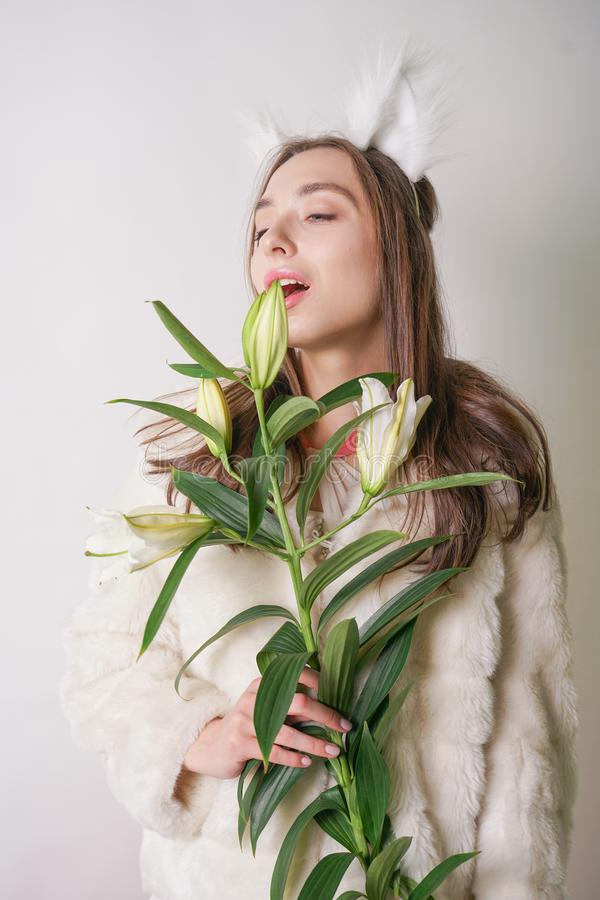 Cute young teen girl standing in a winter warm fur coat and cat furry ears on her head, she holds a branch of fresh lilies. woman royalty free stock photo