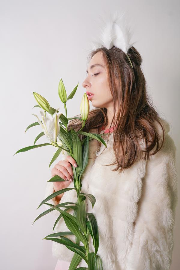 Cute young teen girl standing in a winter warm fur coat and cat furry ears on her head, she holds a branch of fresh lilies. woman royalty free stock photos