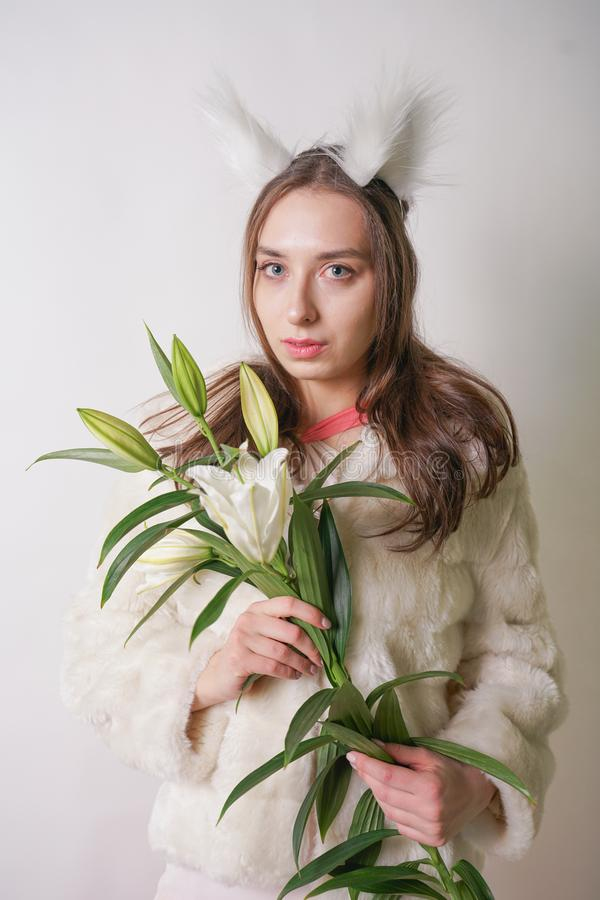 Cute young teen girl standing in a winter warm fur coat and cat furry ears on her head, she holds a branch of fresh lilies. woman stock photo