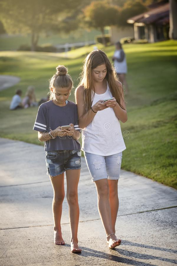 Cute young teen girls texting on their mobile cell phone outdoors. Teenage friends connecting with the world around them on their cell phones royalty free stock photo