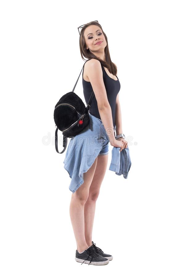 Cute young teenage woman posing with jacket tied around waist with black plush bag. royalty free stock image
