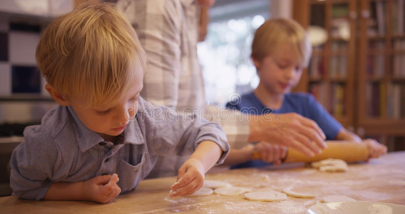 Cute young white boy spreading powder over cookie dough.  stock images