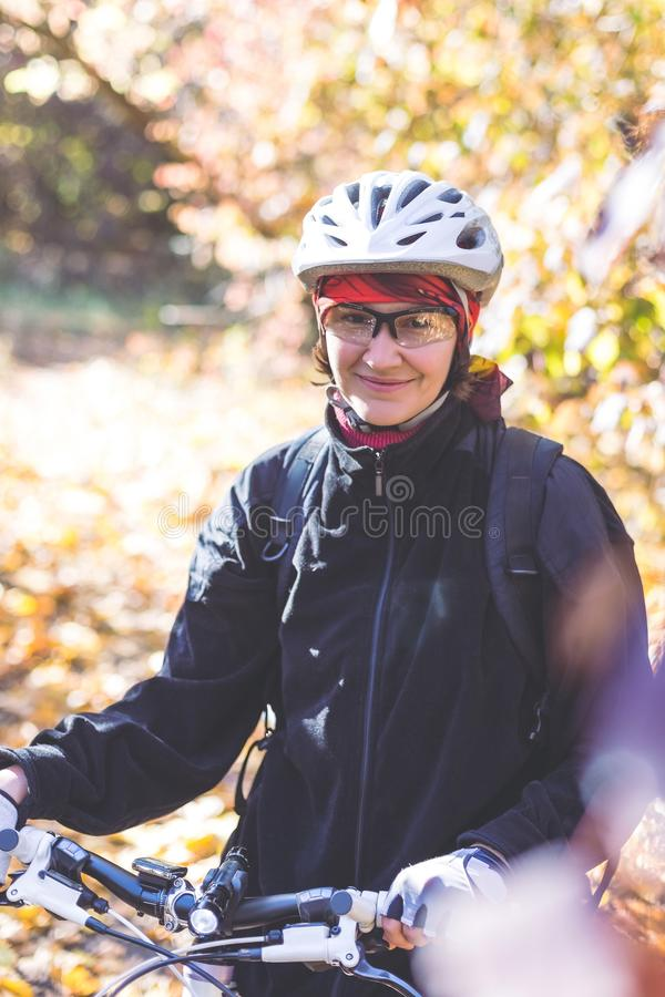 Cute young woman on a bicycle in the autumn forest royalty free stock photo