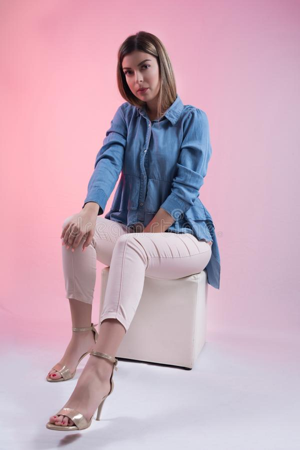 Cute young woman in blue jeans shirt and high heels on leg sitting on white cube stool in studio and isolated on pink stock photo