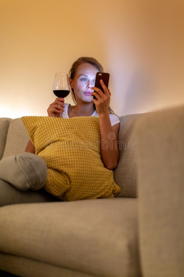 Cute young woman on a comfortable sofa in her modern apartment stock photo
