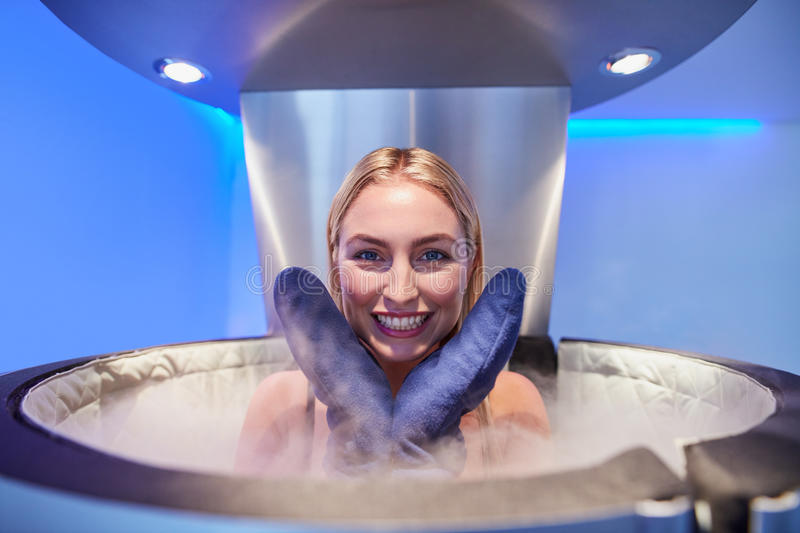Cute young woman in cryosauna booth royalty free stock images