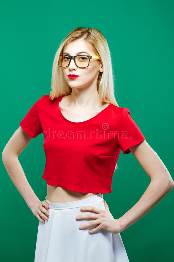 Cute Young Woman with Eyeglasses, White Skirt and Red Short Top is Posing Looking at the Camera. Beautiful Girl Portrait. Cute Young Woman with Eyeglasses, White stock photography