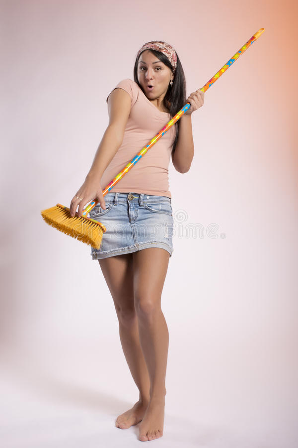 Playful Young Housewife With A Broom Royalty Free Stock Image
