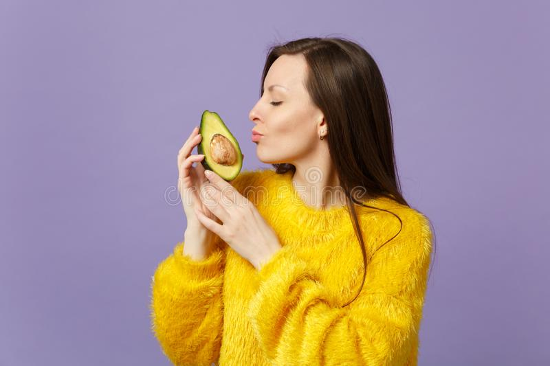 Cute young woman in fur sweater keeping eyes closed holding, kissing half of fresh ripe avocado isolated on violet royalty free stock image