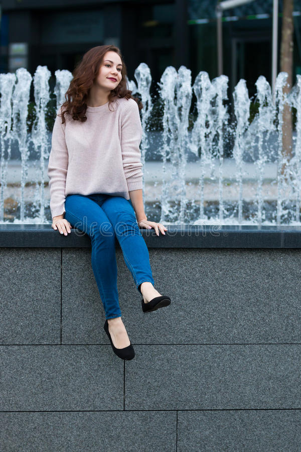 Cute young woman having fun next to fountain on street of the city royalty free stock photography