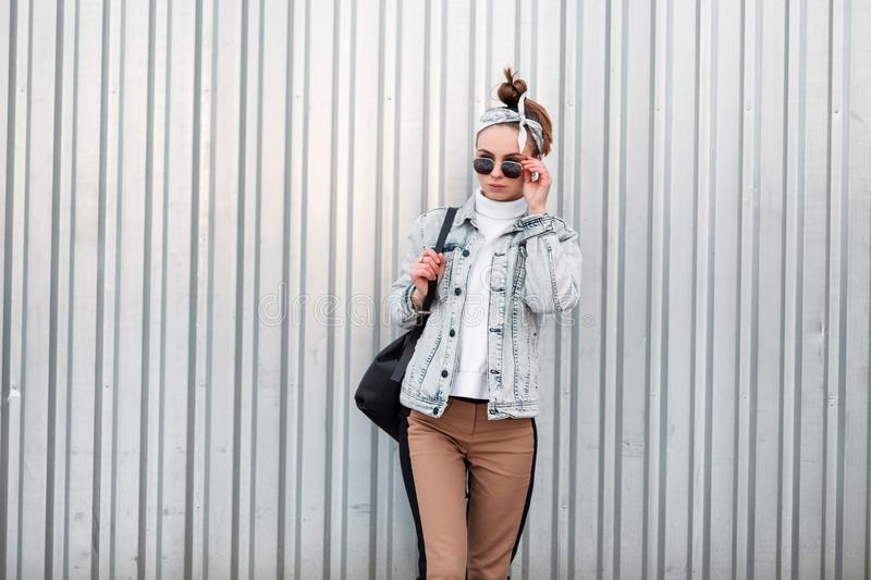 Cute young woman hipster with a stylish hairstyle in a trendy bandana in a knitted vintage sweater in a denim jacket. In stylish pants with a black backpack royalty free stock photo
