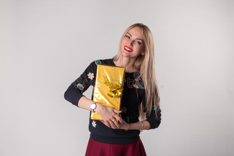Cute young woman holding gift box in her hands royalty free stock image