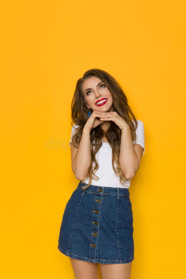 Cute Young Woman In Jeans Mini Skirt And White Top Is Looking Up And Dreaming. Lovely young woman in jeans mini skirt and white top is holding hand on chin royalty free stock photos