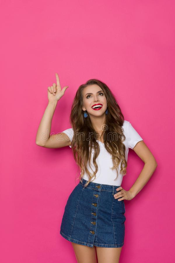 Happy Young Woman In Jeans Mini Skirt And White Top Is Looking Up And Pointing. Cute young woman in jeans mini skirt and white top is looking up, pointing and royalty free stock image