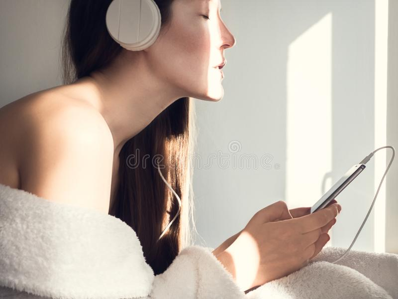 Cute, young woman listening to music. On her mobile phone after a spa treatments stock images