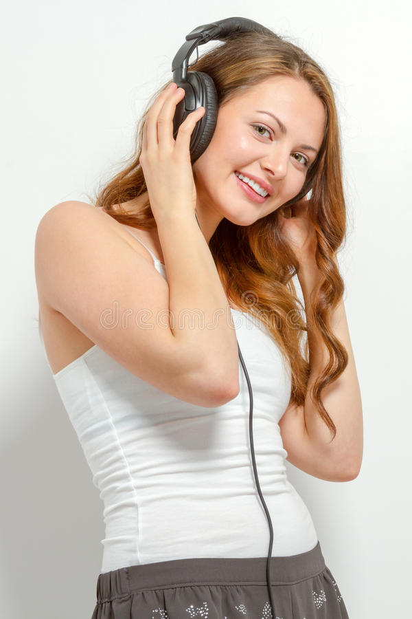 Cute young woman listens to headphones stock images