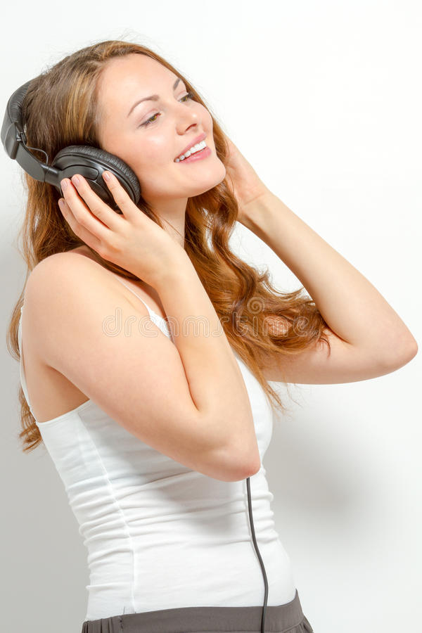 Cute young woman listens to headphones royalty free stock photo
