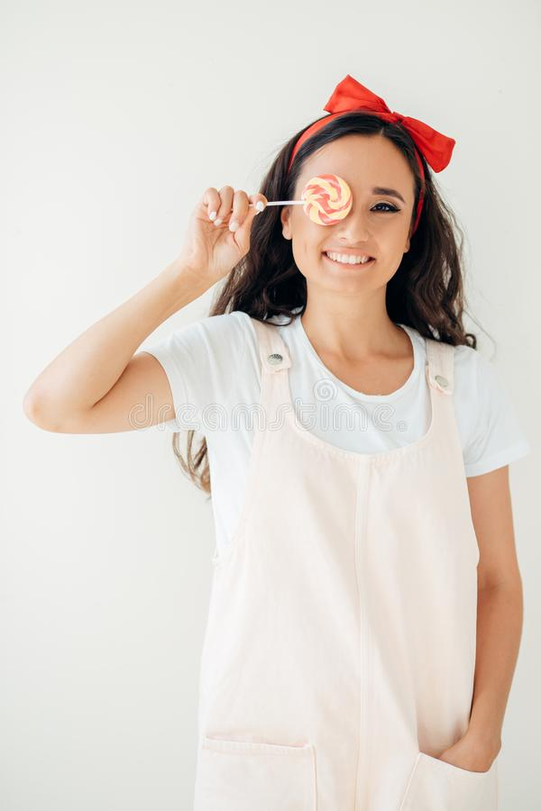 Cute young woman looking into the camera and holding a lollipop against her eye.  royalty free stock image