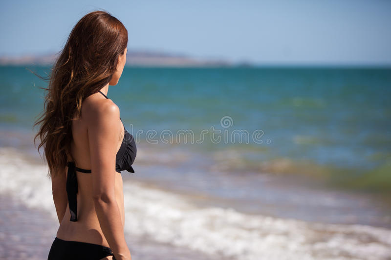 Cute young woman looking at the sea. Brunette in a bikini looking at the ocean on a sunny day stock images