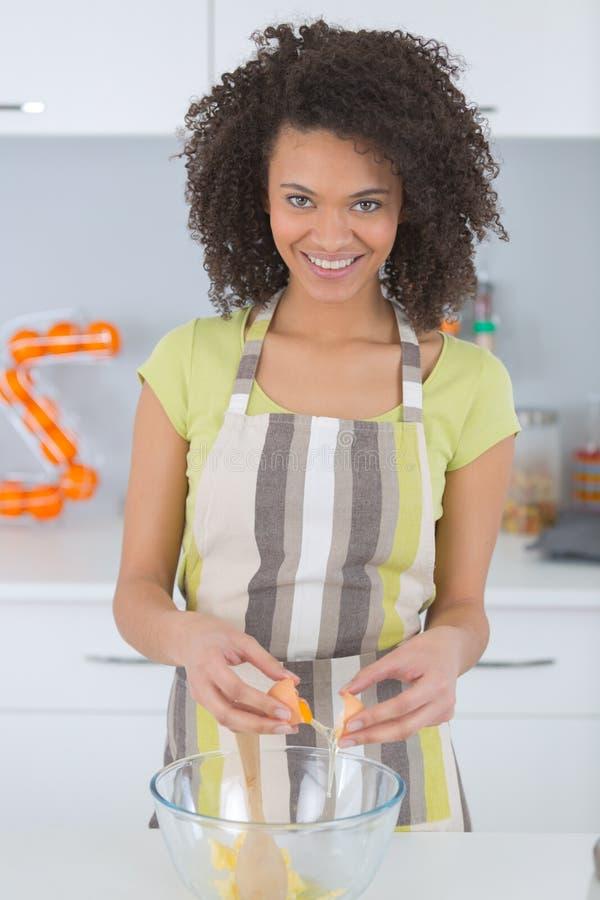 Cute young woman making dough in kitchen stock photo