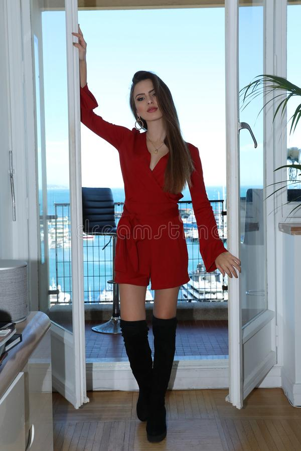 Cute Young Woman Model Posing In Red Dress In A Luxurious Apartment In Monaco stock photography