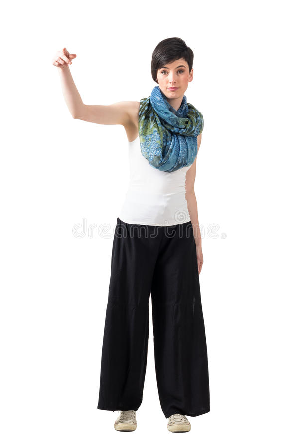 Cute young woman pointing finger at camera in gangster posture. Full body length portrait isolated over white studio background stock photography