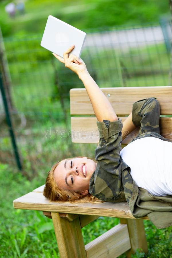 Cute young woman relaxing on a wooden bench. In the garden lying on her back holding aloft a tablet-pc royalty free stock photo