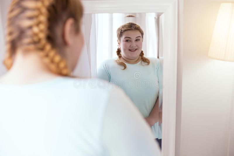 Cute young woman showing her little dimple. Cute dimple. Plump smiling woman turning left to the mirror showing her dimple royalty free stock images