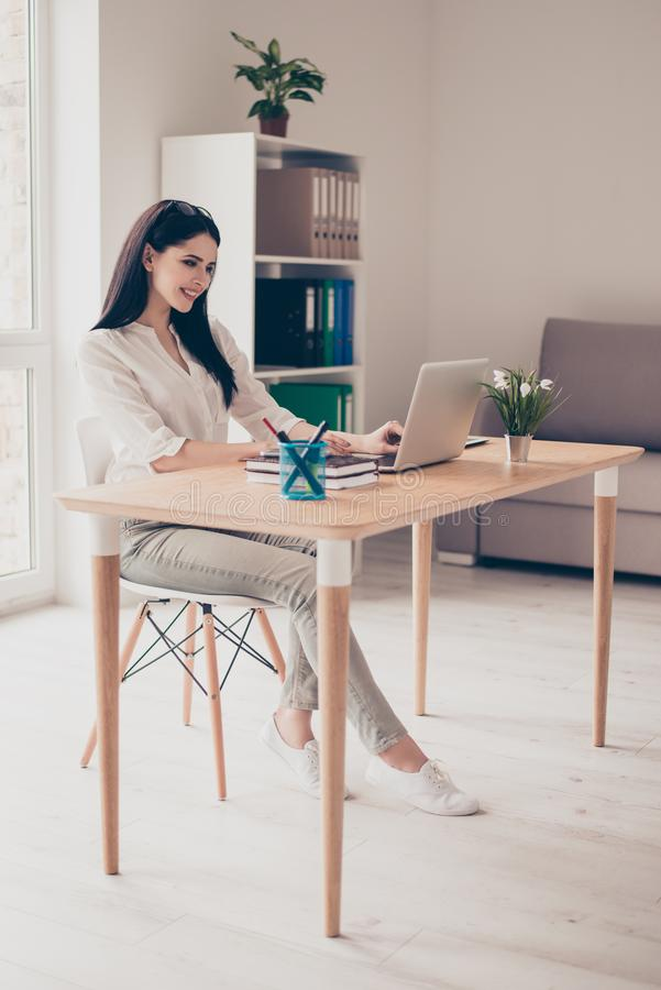 Cute young woman sits at the desk in the office, works with la stock photography