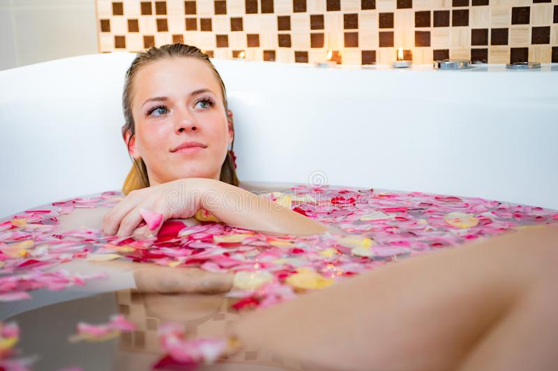 Cute young woman sitting in bathtub with rose petals royalty free stock images