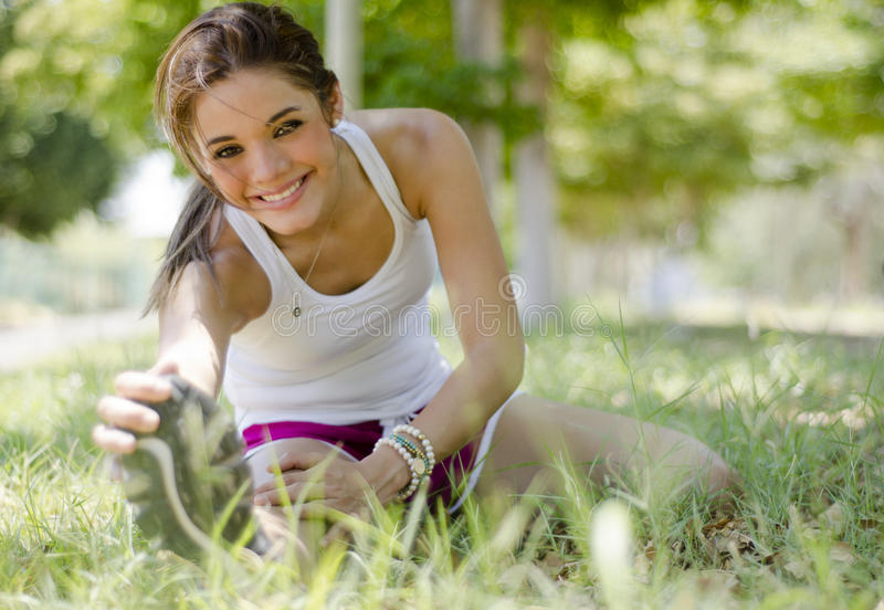 Cute young woman stretching. Beautiful young woman stretching and warming up before exercising royalty free stock images