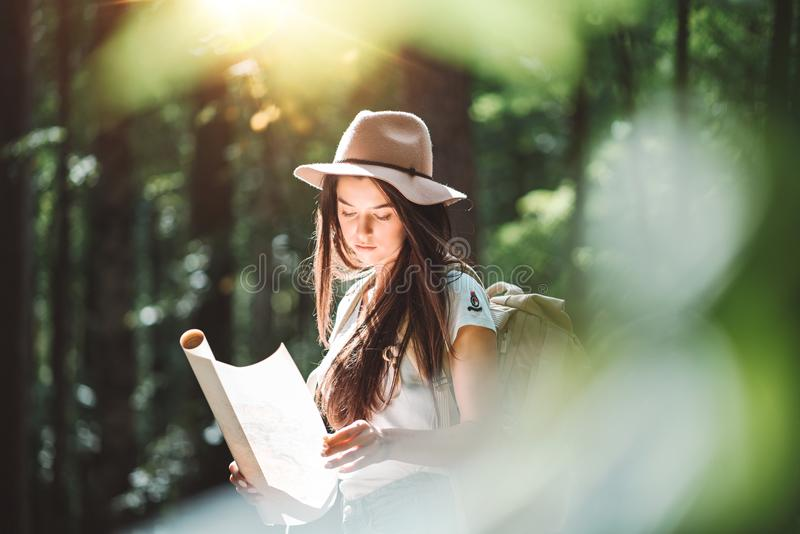 Cute young woman wearing hat and backpack hold location map in hands and searching way for travel. Handsome young girl traveling among trees at sunset royalty free stock images