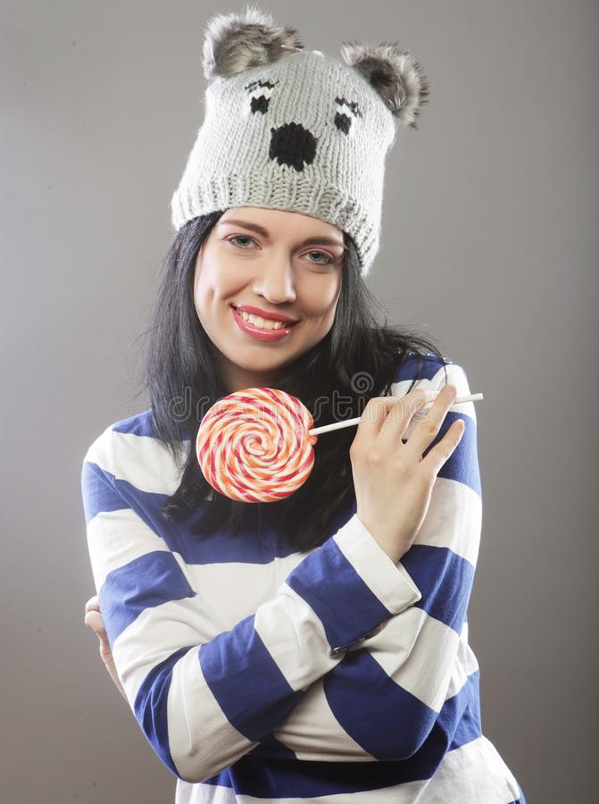 Woman wearing hat looking into the camera and holding a lollipo. Cute young woman wearing hat looking into the camera and holding a lollipop royalty free stock photos