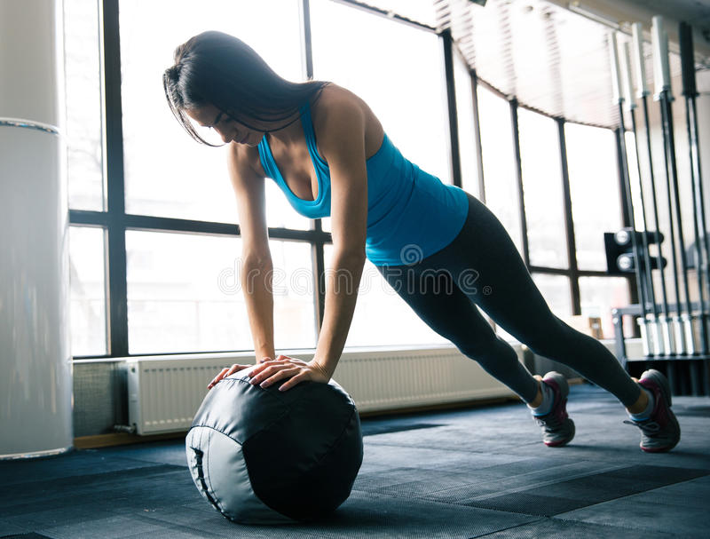 Cute young woman working out with fit ball stock image