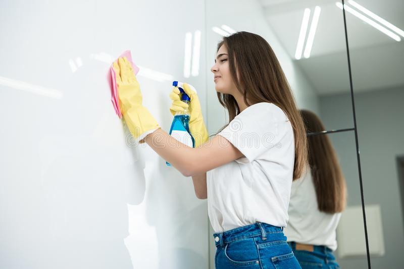 Cute young woman in yellow gloves with detergent spray in her hand wiping dust off from the kitchen wall with a rag thoroughly.  stock images
