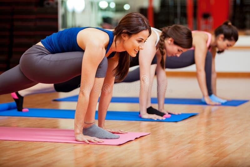 Cute young women doing yoga royalty free stock photos
