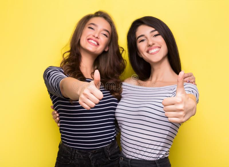 Cute women friends showing thumbs up on yellow background stock photo
