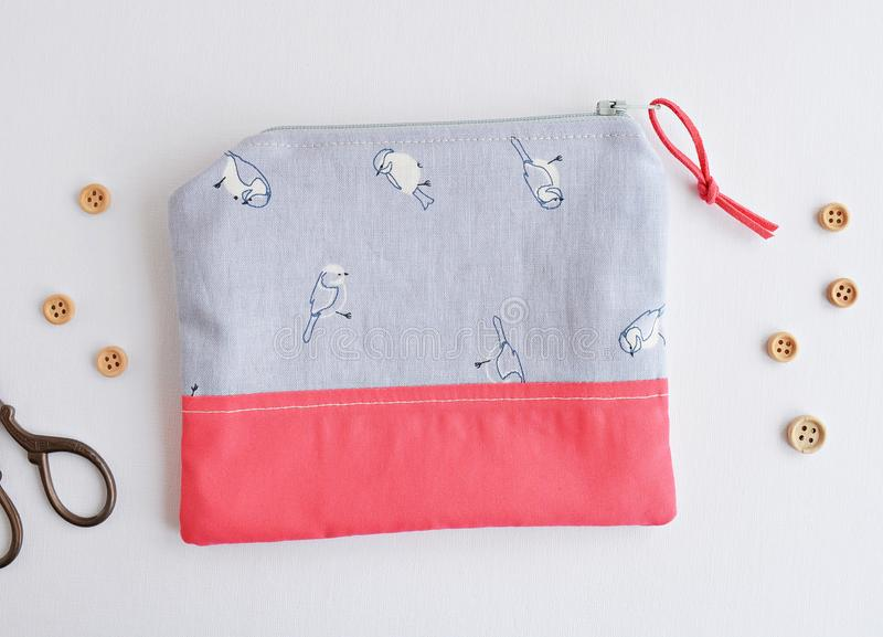 Cute zipper pouch with birds. Thread, scissors and buttons royalty free stock photography