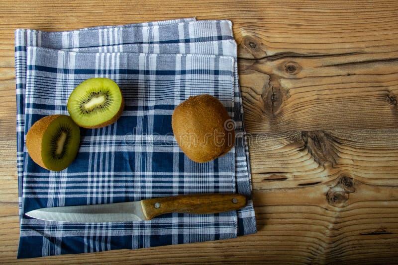 Cuted猕猴桃准备好为在木桌和古色古香的刀子中吃 免版税图库摄影