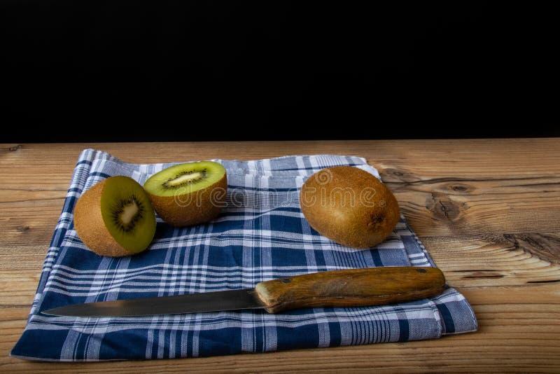 Cuted猕猴桃准备好为在木桌和古色古香的刀子中吃 免版税库存照片