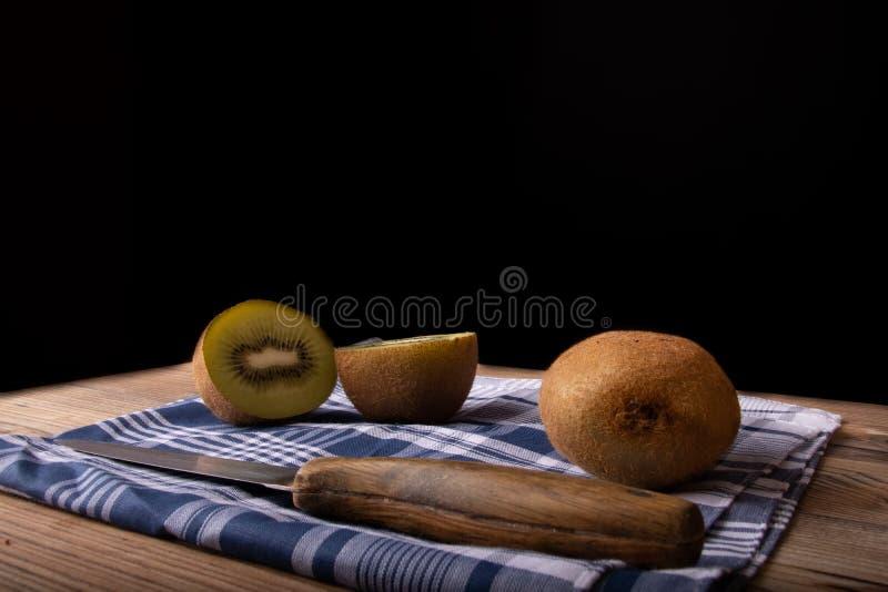 Cuted猕猴桃在与刀子和黑背景的木桌里 图库摄影
