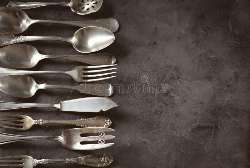 Cutelaria antiga do vintage - forquilhas, colheres, facas e outro em um fundo preto fotos de stock royalty free