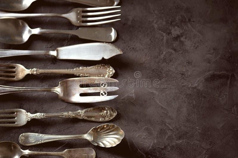 Cutelaria antiga do vintage - forquilhas, colheres, facas e outro em um fundo preto fotografia de stock