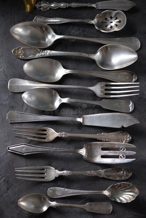 Cutelaria antiga do vintage - forquilhas, colheres, facas e outro em um fundo preto imagens de stock