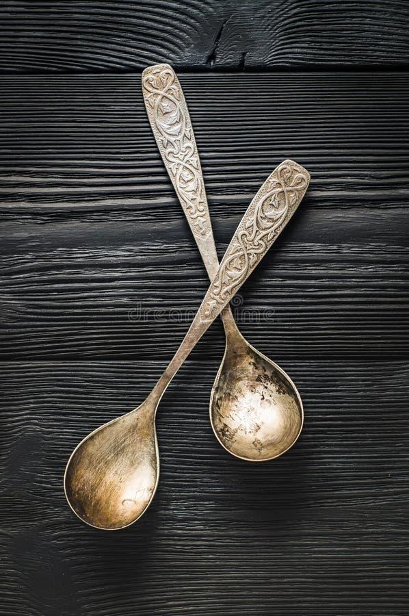 Cutelaria: colheres de prata em placas escuras foto de stock royalty free