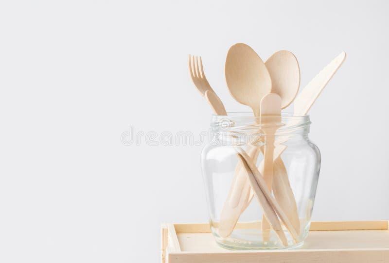 A cutelaria de madeira dá a faca da forquilha em um frasco de vidro no fundo branco da parede Eco reusável livre plástico do desp foto de stock