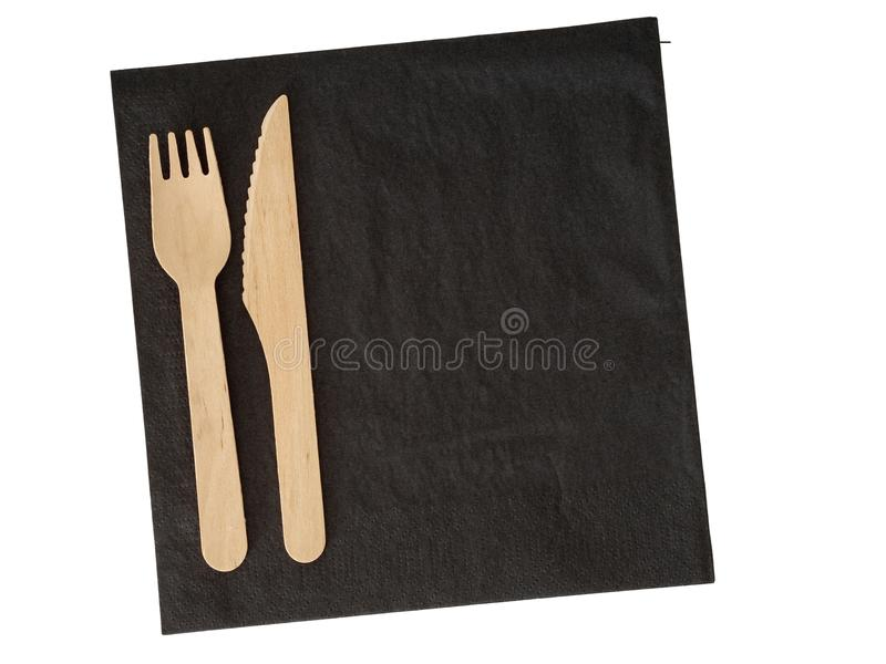 Cutelaria descartável de madeira no serviette preto Isdolated no branco Ecofriendly fotografia de stock royalty free